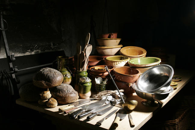 A kitchen table filled with bread, kitchen knives and lots of Tudor ceramic bowls and plates that are stacked on top of each other.