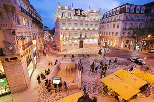 A square in Lisbon, Portgual with stairs down to the subway, people and cafe tables