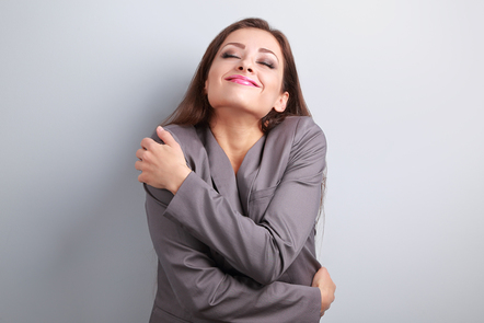 Happy business woman hugging herself.