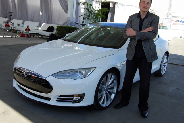 Elon Musk standing in front of a Tesla car