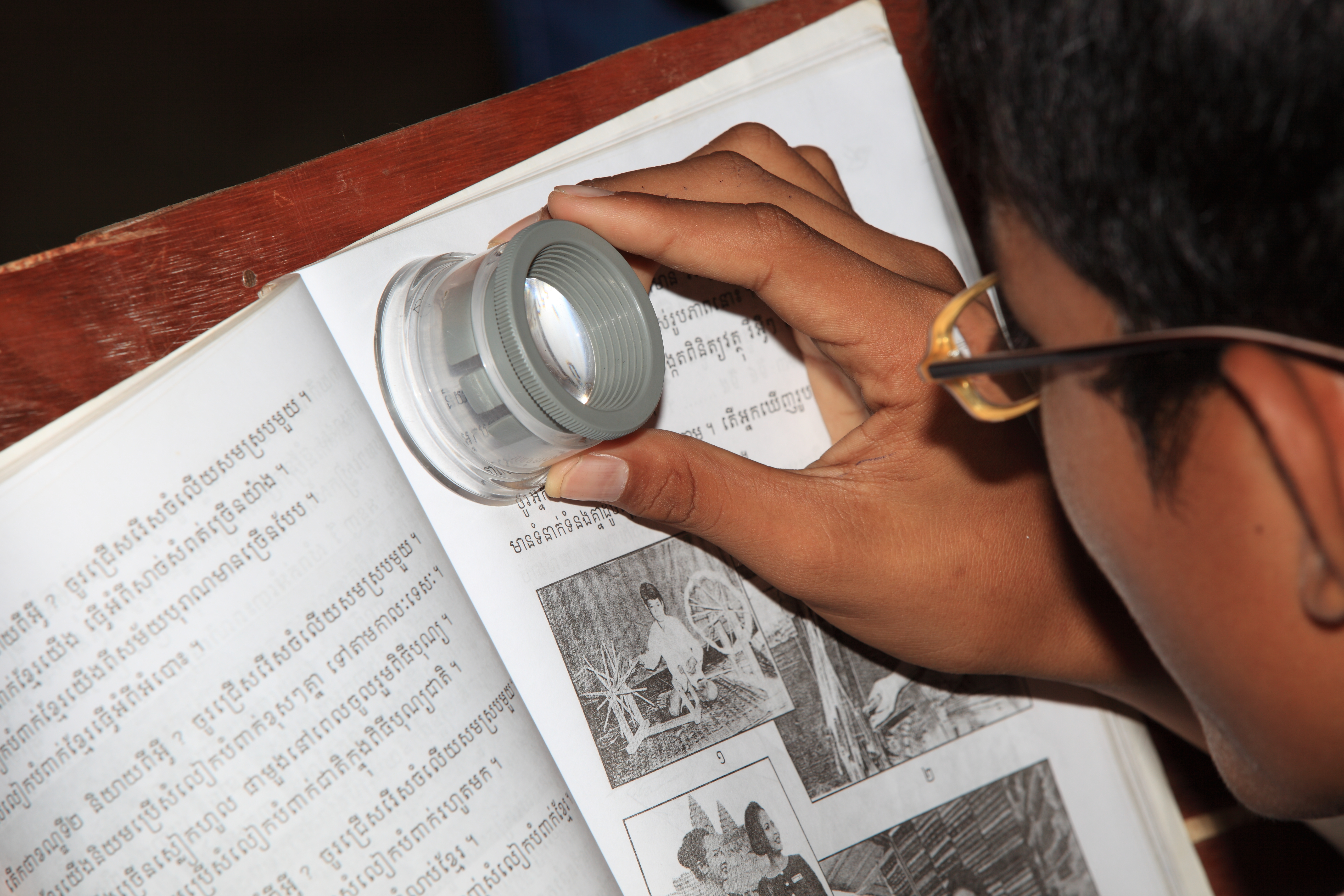 Using a stand magnifier to read writing on the pages of a book