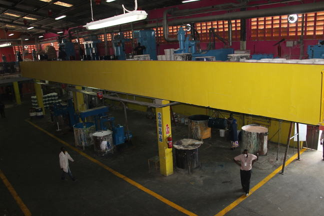 Inside a paint factory, showing machines for mixing paint