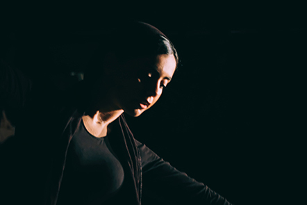 female performer in darkness, face lit
