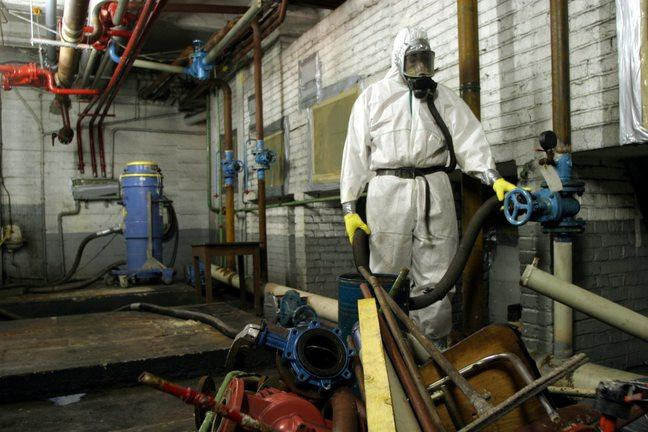 Worker in protective clothing while handling asbestos fibres