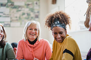 Close-up image of two social care workers, both smiling