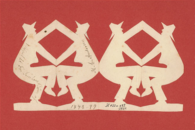 A Hans Christian Andersen paper cut showing four men touching hands and knees two and two