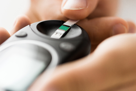 Close up of man checking blood sugar by glucometer.