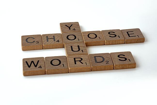 Scrabble tiles spelling out 'choose your words'