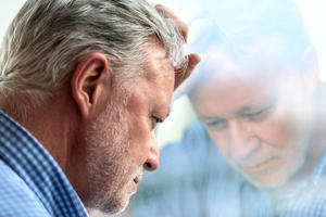 Older man with head up against window, thinking and looking concerned.