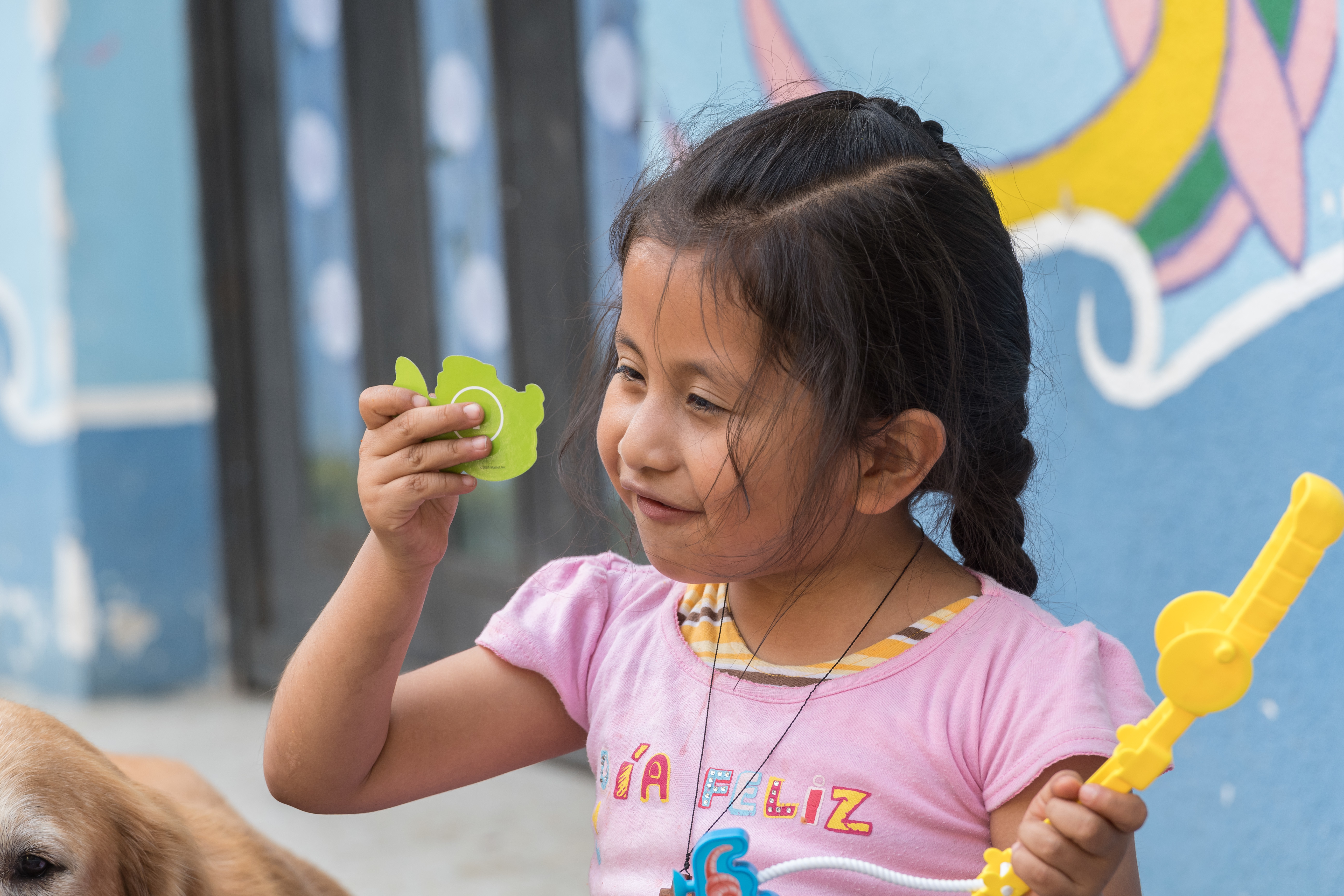 A young girl looks closely at a small green object in her hand