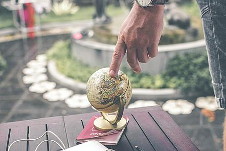 a photo of a person pinpointing a specific geographic location on a globe