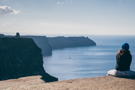 A woman sitting on the edge of the Cliffs of Moher, Co. Clare.