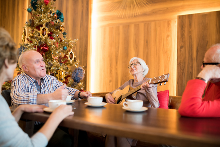 Four elderly people are sat around a table while one of the females is playing an acoustic guitar