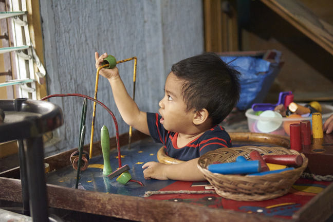 A young boy with cerebral palsy playing with toys.