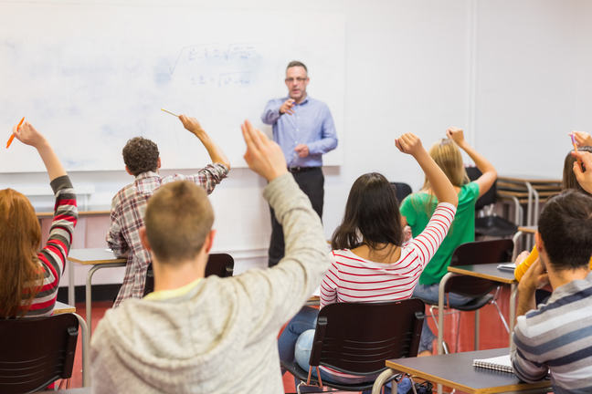 A teacher pointing to a student with their hand raised