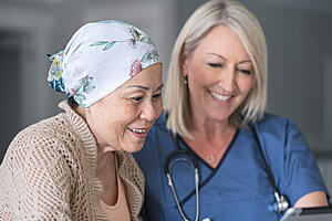 An elderly cancer patient and a medical practitioner