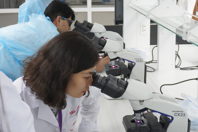 Learner looking through the microscope in a lab
