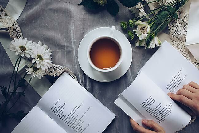 In this image, there is a table on which a book of poetry is placed, a vase of flowers, and a cup of tea. There are also a pair of hands on this table, which are following a line of poetry in a second book.