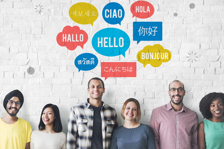 A multicultural group of men and women stand smiling in front of a white brick wall. The word 'Hello' is written in different languages and colours on the wall.