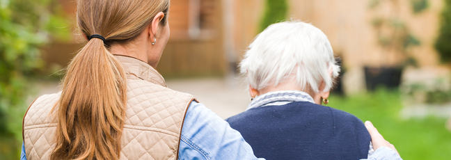 A carer supports an elderly woman with dementia