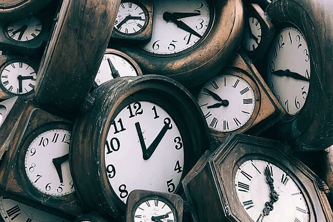A vast number of old wooden clocks stacked around each other.