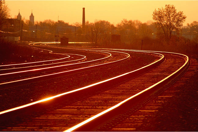 Image is of a train track at sunset.