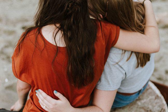 2 vrouwen met hun arm om elkaar heen