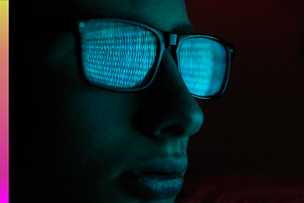 An image of code reflecting on a hacker's glasses.