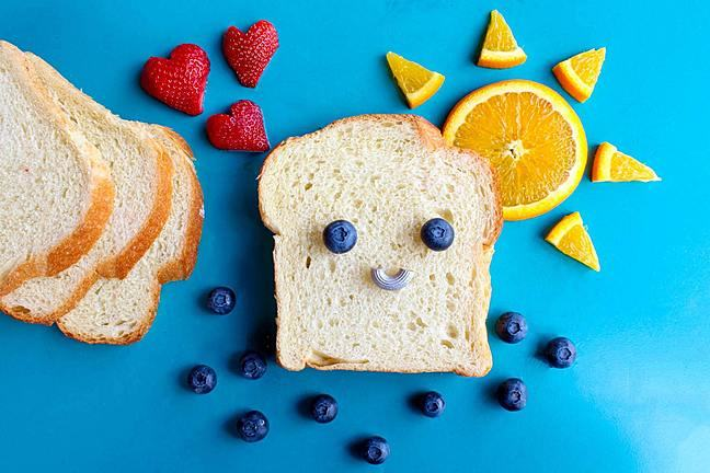 A slice of white bread against a blue background, where a smiley face has been made on the slice using two blueberries and half a polo mint. Arranged around the face are orange pieces in the shape of a sun, 3 strawberry hearts and various blueberries.