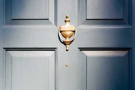 A blue door, with a gold knocker bathed in sunlight.