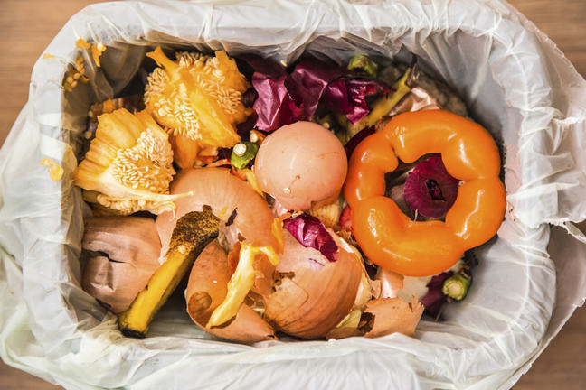 An aerial photo of a bin filled with vegetable peeling and cores