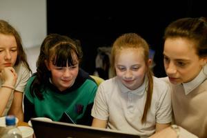 A female teacher and three girls looking at a computer screen