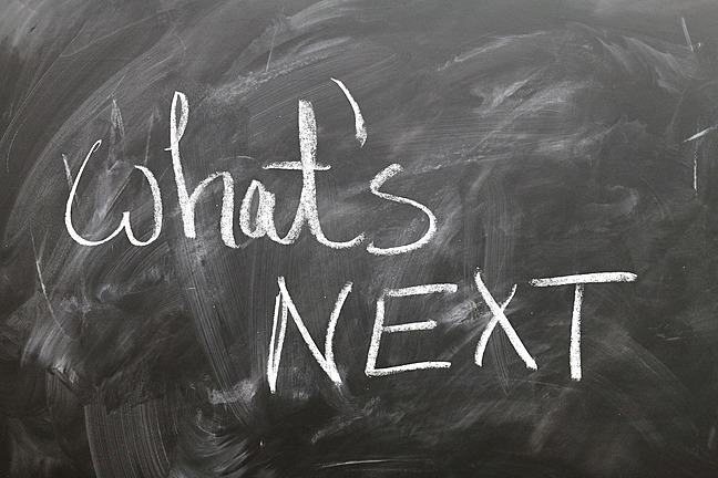 black board with the words what's next written in white