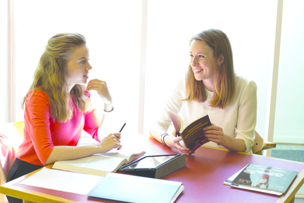 Two ladies sitting around a desk with text books in from of them, smiling and looking at each other