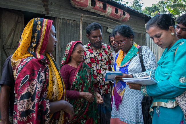 Masura Begum, age 35 of Purba para, Charitabari is receiving referral slip for relief. Mita Alam of CBM local partner GUK is seen signing the slip after making physical visit to masura magums house.