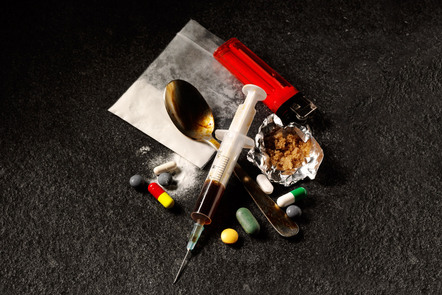 A syringe, spoon, lighter, pills and other items associated with drugs and addiction