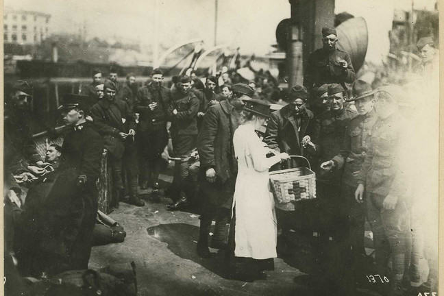 Image of female medical worker offering supplies to sick and wounded soldiers