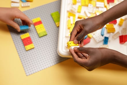 Image of children's hands playing with LEGO Braille Bricks