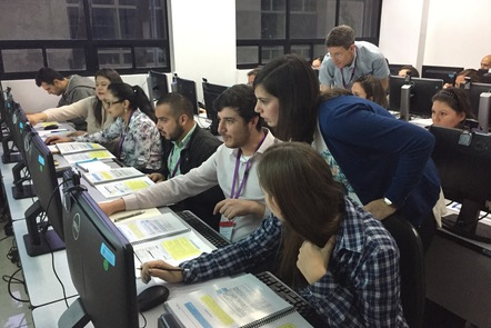 Learners in computer lab with an Educator helping