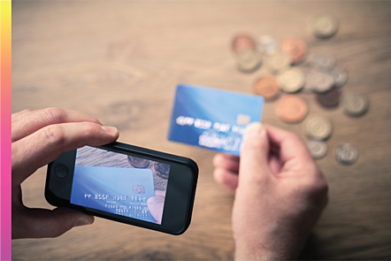 Photographic image of a mobile phone being used by a man to take a photo of a credit card