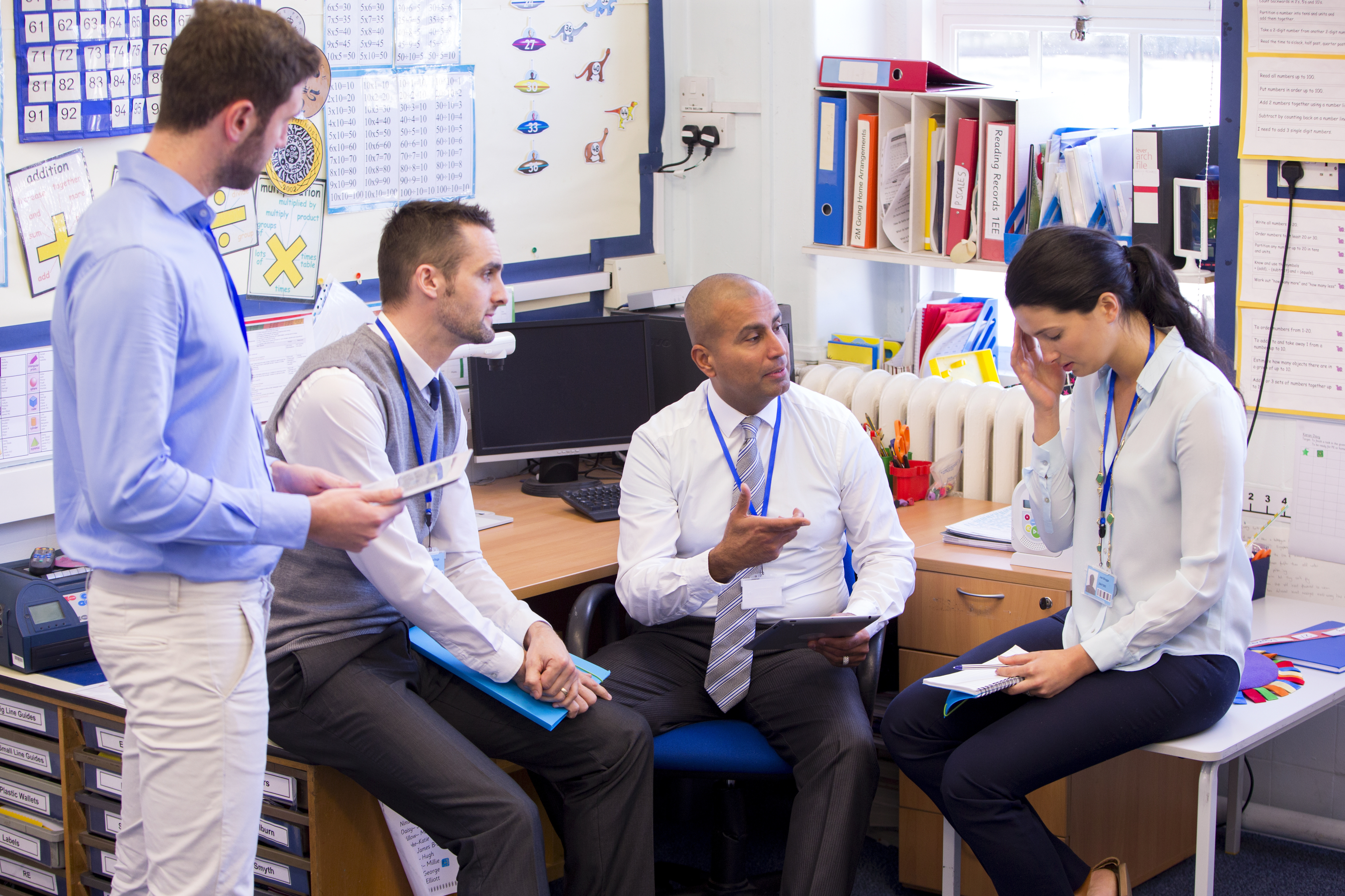 Teachers support a stressed colleague in the staffroom.