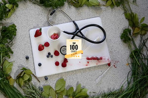 Chopping board with stethoscope and berries in a test tube, including Class Central badge Top 100 Course of All Time