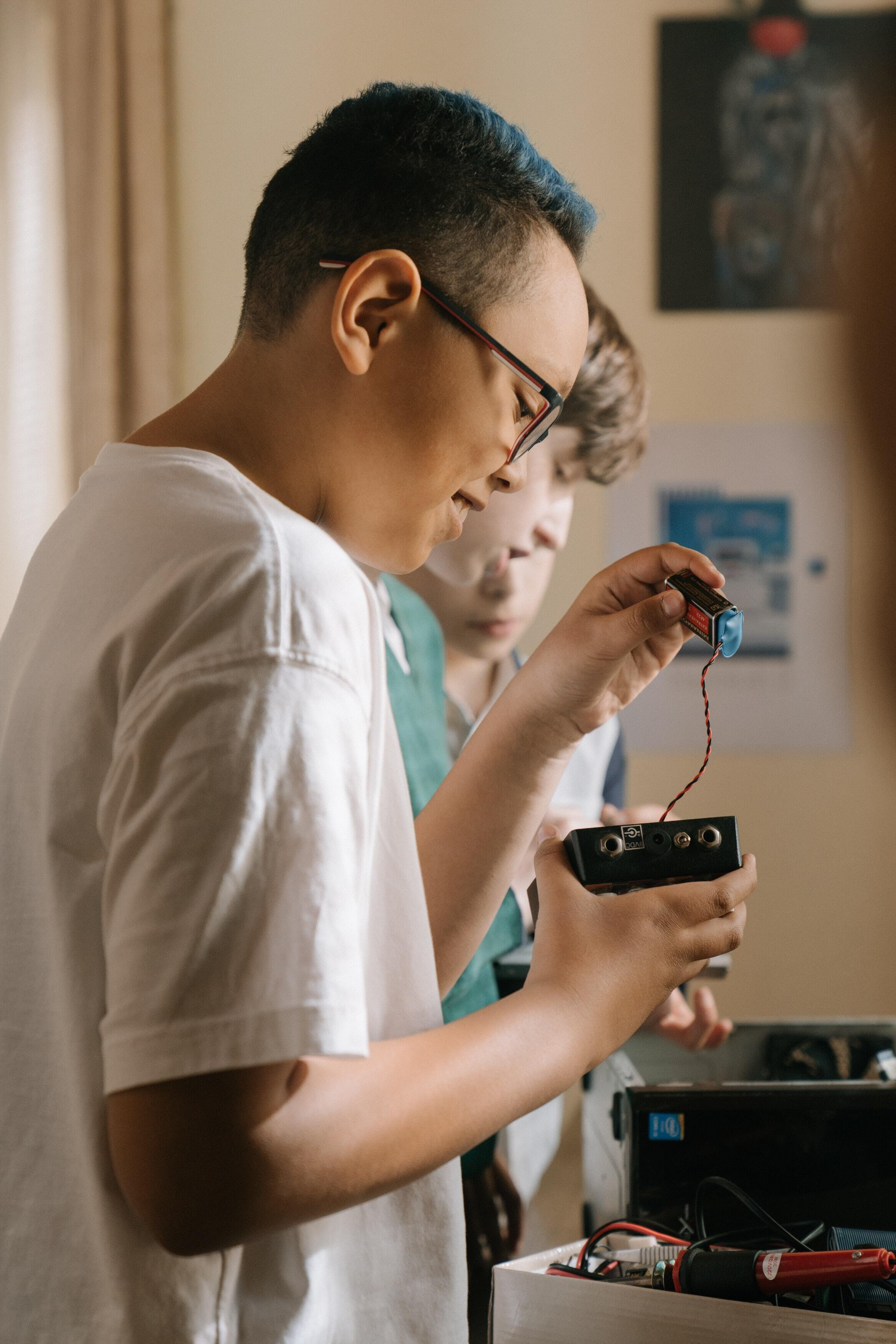 a young boy connecting a battery to a device