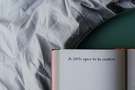 A notebook open on a bed. The heading on the top of the notebook reads 'A little space to be creative'.