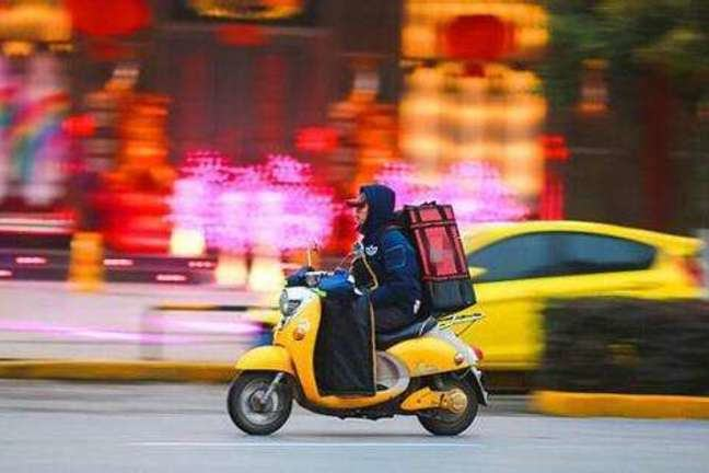 A man rides an electric bike to deliver take-out