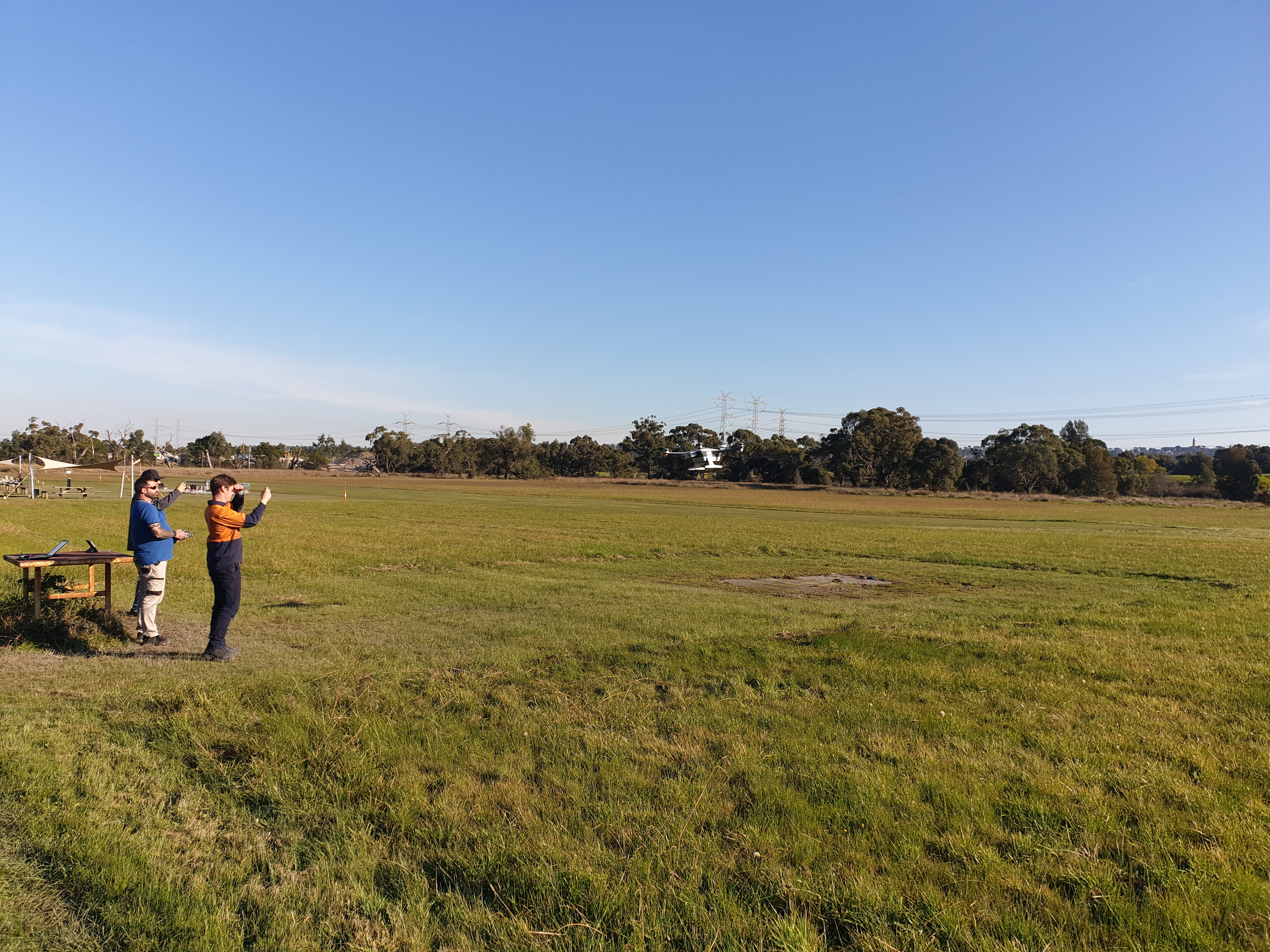 A person being trained to operate a drone in a wide field.