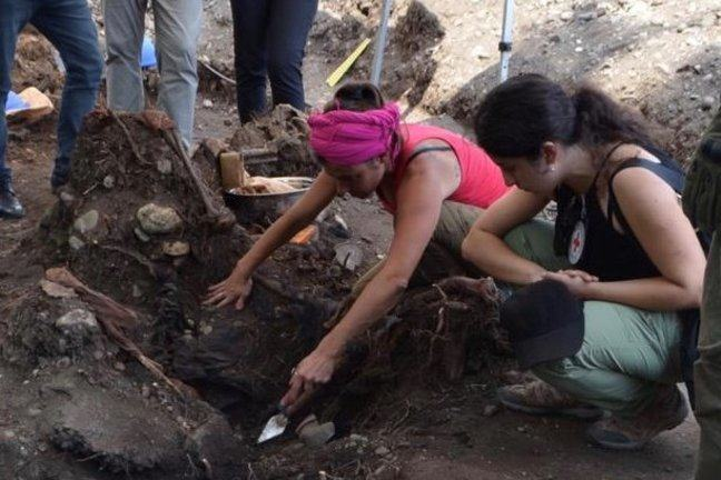 A forensic scientist excavating a grave site