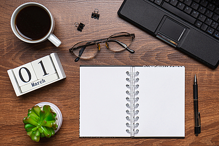 A modern office workspace with laptop keyboard, coffee cup, smart phone, stationery and plant. Date 01 March on wooden block calendar. White empty notepad page. Table desk top view, flat lay, copy space
