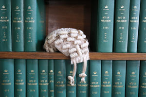 Traditional judge's wig on a bookshelf full of bound copies of acts of parliament