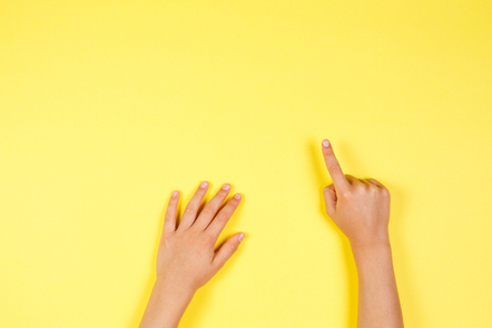 A pair of hands on a yellow canvas, with one pointing forward
